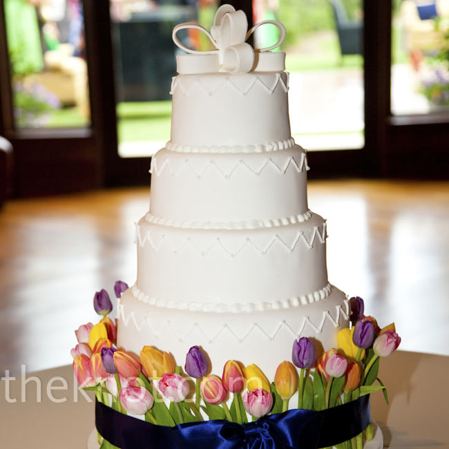 A nod to the garden setting, fresh tulips decorated the base of the tall, white cake. Bows at the top and bottom added more detail.