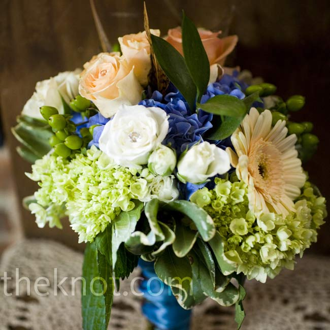 Soft pheasant feathers added a rustic touch to the hydrangea, gerbera daisy, rose, and hypericum berry bridesmaid bouquets.