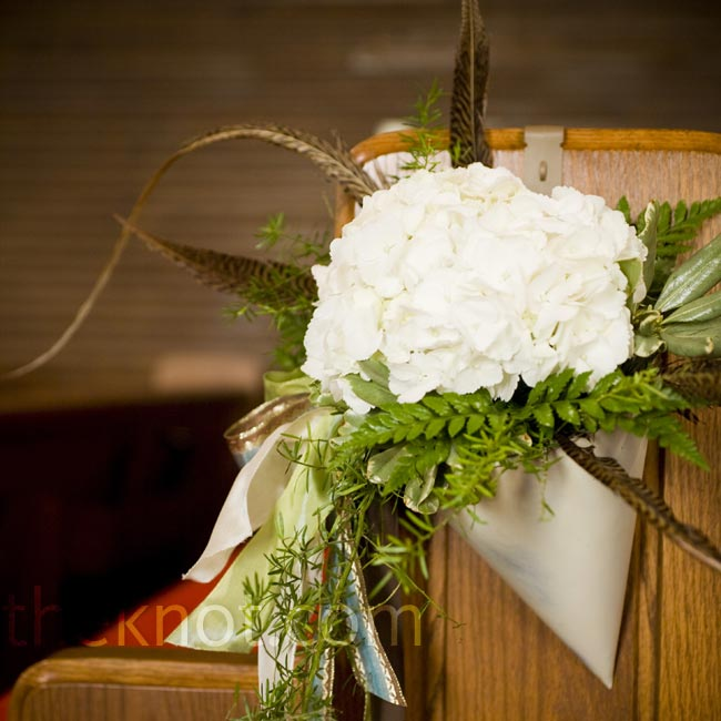 Painted tin cones filled with ivory hydrangeas and pheasant feathers decorated the ends of the church pews.