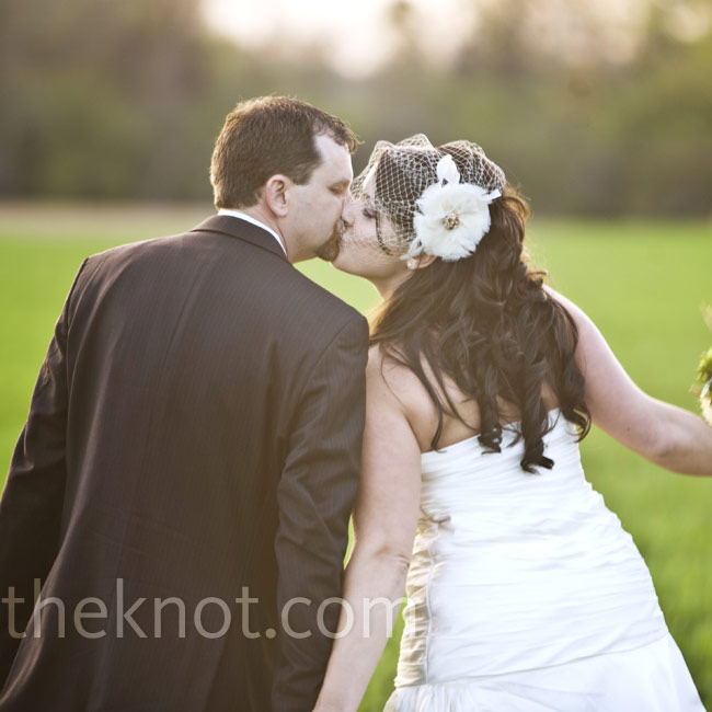 """A feather headpiece and cage veil were the perfect complement to the bride's Stephen Yearick gown. With a flattering ruched bodice and chapel train, """"It was both elegant and comfortable,"""" says Harley."""