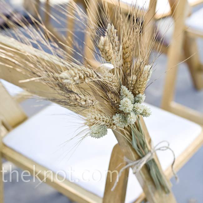 Every aisle chair was decorated with dried grain bound with twine. They shared a similar rustic look with the bride's bouquet.