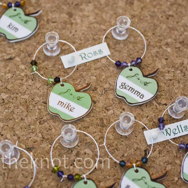 Apple-shaped wine charms hung from a corkboard next to the glasses. They were personalized with each guest's name to help keep their drinks straight.