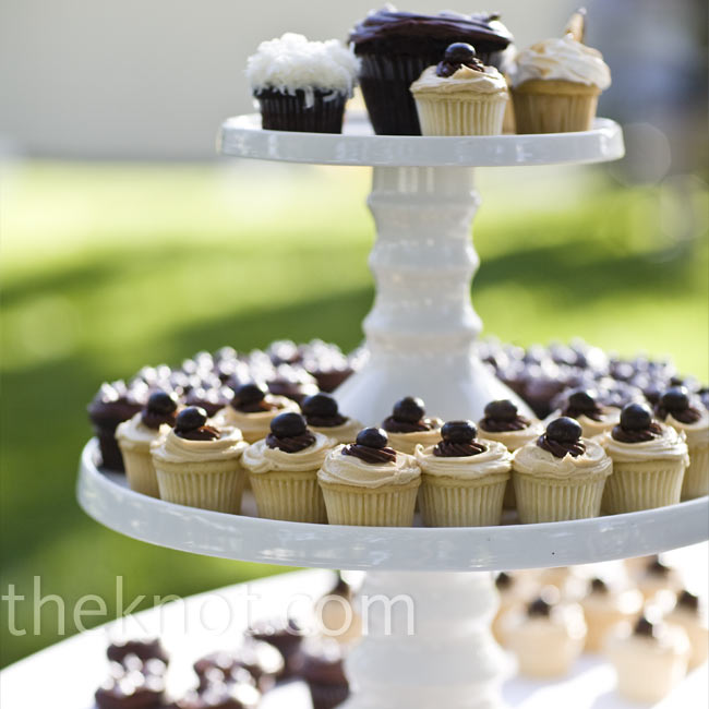 The couple chose four flavors of mini cupcakes. Instead of cutting into a small cake, the newlyweds sliced a large chocolate cupcake at the top