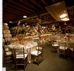 Orange centerpieces and twinkle lights brightened up the venue. The neutral-toned linens paired well with the exposed beams and wine barrels in the space.