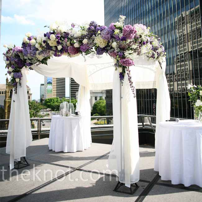 A huppah draped with white chiffon and accented with hydrangeas and roses defined the space where the couple exchanged vows.