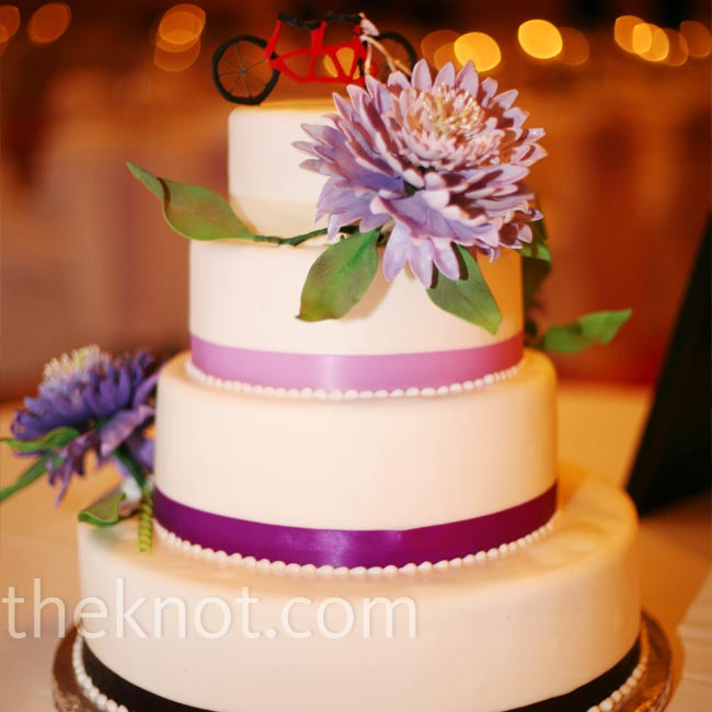 The three-tiered cake was covered with fondant and trimmed with purple ribbon. Sugar-made purple flowers and a small tandem bicycle cake topper finished it off.