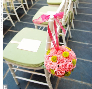 The ceremony space was already perfect with a fountain, flowers, and trees, but a few carnation and mum pomanders tied to white chairs with lime green cushions pulled the look together.
