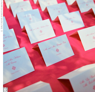 The brilliant pink linens atop the escort card table matched the ink on the simple white escort cards.