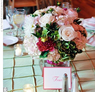 Low vases filled with pink, green, and ivory flowers like roses, hydrangeas, and dahlias, sat atop every other table.