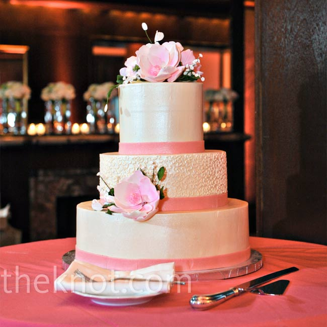 Realistic-looking pink-and-green sugar flowers adorned the top and sides of the three-tiered cake. Pink strips of fondant around each tier mimicked the ribbon used throughout the décor.