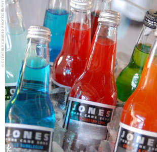 Instead of flowers, the couple used functional centerpieces on the dinner tables. They filled clear, plastic tubs with bottles of bright Jones Soda and ice.