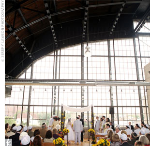 Natural light shone in through the floor-to-ceiling windows for the couple's morning ceremony. Sunflowers added color along the aisle.