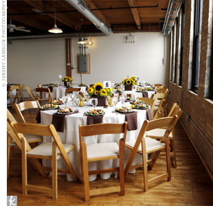 The potted sunflowers from the ceremony doubled as table centerpieces in the rustic reception room.