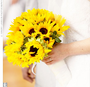 Robyn carried a bouquet of sunflowers wrapped in white fabric to complement her gown.