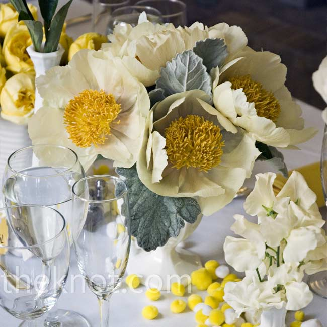 The couple collected over 100 pieces of vintage milk glass to hold peonies, ranunculus, and sweet peas. Pom-poms on the tables upped the fun factor.