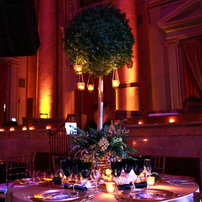 Towering topiaries with candles, gold-dusted grapes, olive leaves, and ivy filled out the vast room.