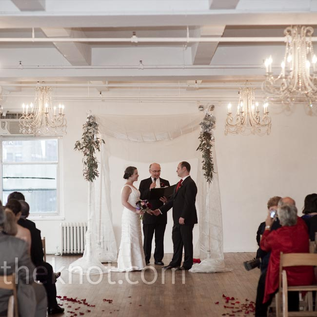 With all of the chandeliers in the space, the couple chose to marry under a simple huppah. Rose petals on the floor brought the signature color into the scene.