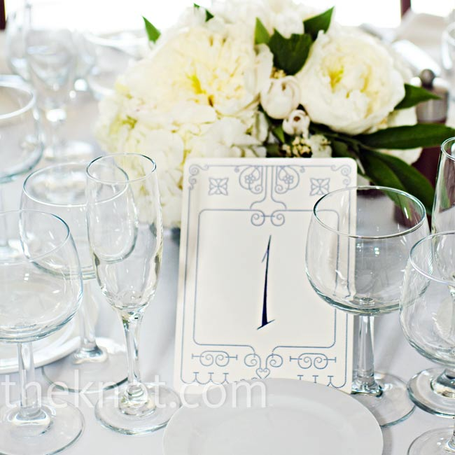 Graphics similar to the ones on the invitations appeared on the table cards. Behind them, all-white peonies and roses decorated the tables.