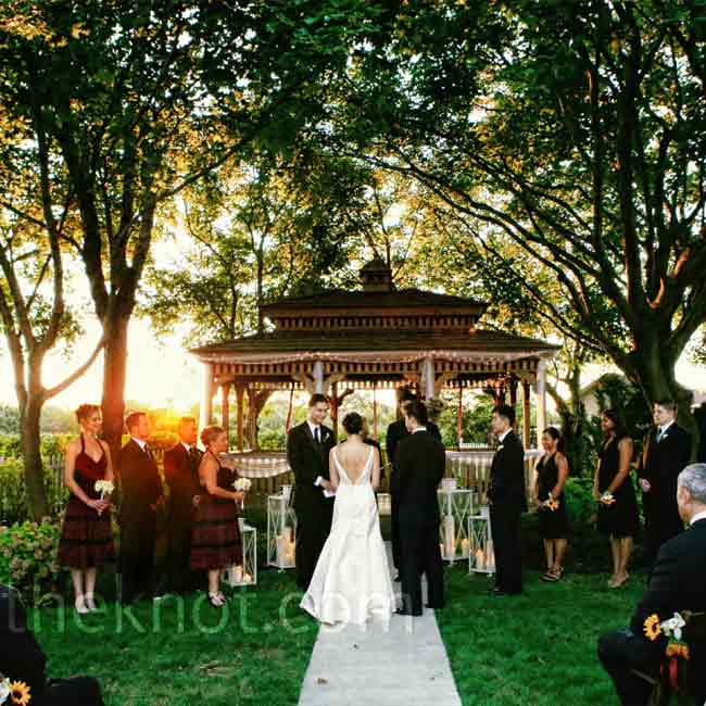 The couple exchanged vows by a gazebo under trees. Guests got front-row seats to watch the sunset.