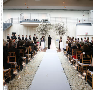 The couple exchanged vows under a huppah made from cherry trees planted in modern, white containers.