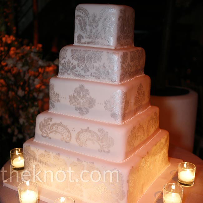 To echo the stationery, a damask print covered the tiers of the square cake. Candles around the base called attention to the silver pattern.