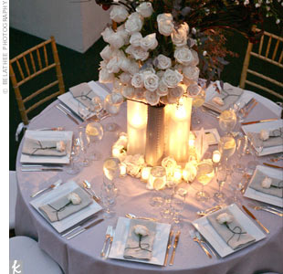 An large arrangement of ivory roses sat atop a cluster of modern vases, enveloped in candlelight. Lavender-gray linens covered the tables and a single ivory rose head adorned each napkin.