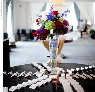 Stephanie and Derek's 200 guests found their seats using ivory-hued escort cards, which featured each name handwritten in purple calligraphy. A tall floral arrangement in the middle of the table gave guests just a hint of what was to come.