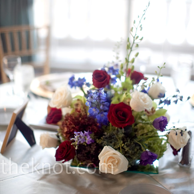Stephanie and Derek's reception tables boasted elaborate floral centerpieces, which included jewel-toned roses, cymbidium orchids, lisianthus, delphiniums, and hydrangeas.