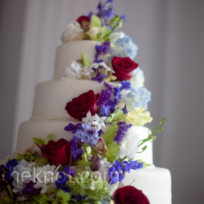 Stephanie and Derek cut into a four-tiered white cake, which featured alternating layers of white cake with lemon filling and amaretto cake with raspberry filling. Fresh flowers in the wedding hues cascaded down the confection's tiers.