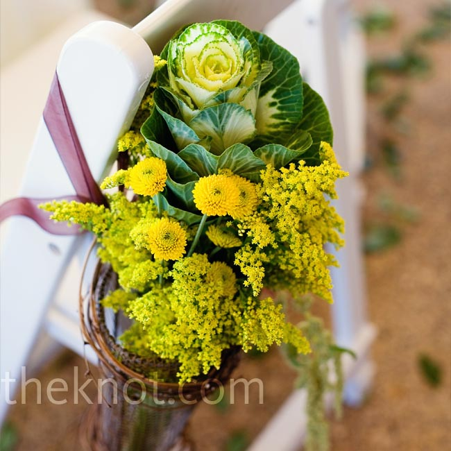 Because the wedding took place outdoors, Holly wanted to emphasize the beautiful green background of the trees and field. The large trees, from which Holly hung small vases from Anthropologie, served as the framing for the ceremony. She placed natural-looking baskets filled with yellow solidago, kale, hanging amaranthus, and brown hypericum berries ...