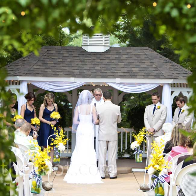 The couple dressed up the ceremony site with simple sheer fabric draped across the gazebo, and four large Mason jars filled with lemons, hydrangeas, craspedia, and orchids hanging from shepherd's hooks.