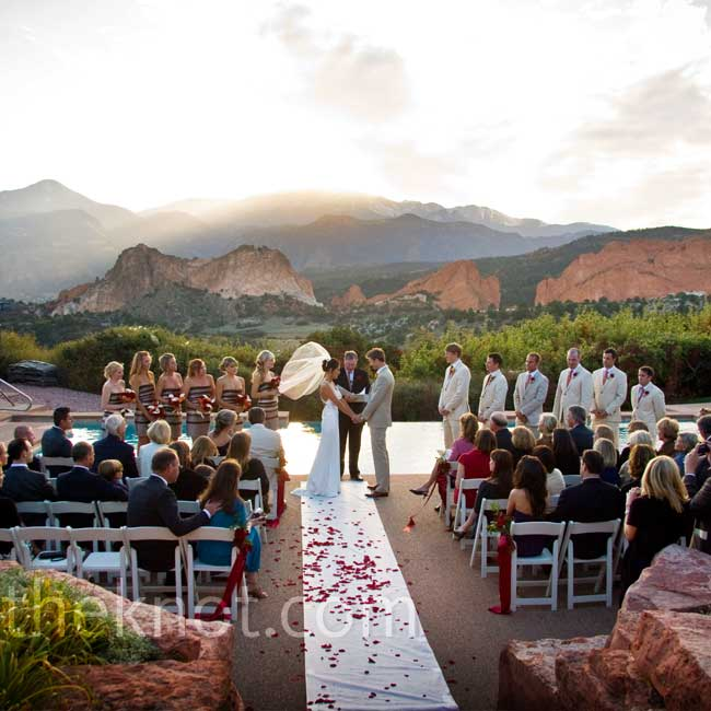 The ceremony took place at the foot of a shimmering pool, with a spectacular view of Pikes Peak and the Garden of the Gods in the background. Kiera walked down an aisle sprinkled with red rose petals as the sun set behind the mountains.