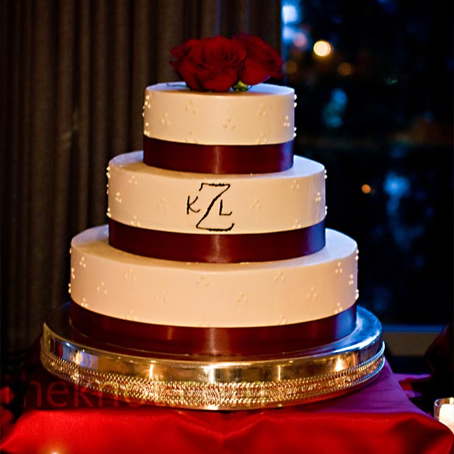 Fresh flowers and deep red ribbon adorned the couple's elegant, monogrammed cake.