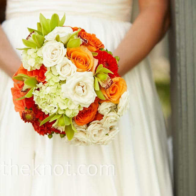 Elizabeth used a piece of lace from her mother's wedding gown to wrap her bouquet of orange and white roses, white hydrangeas, and lime-green orchids. She adorned it with a six pence and vintage rhinestone brooches.