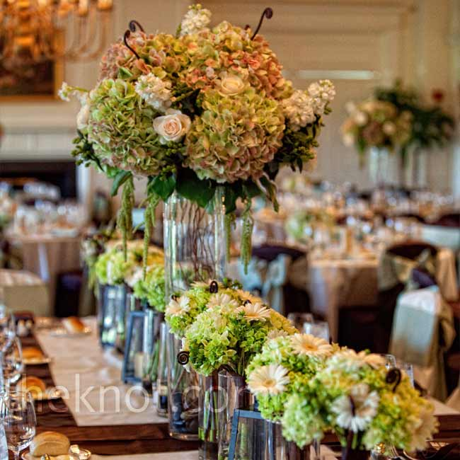 Alternating low and high centerpieces of antique green hydrangeas, roses, stock, berries, fiddlehead ferns, and hanging amaranthus (only in the tall ones) gave the reception tables an elegant look.