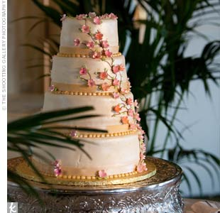 Instead of a topper, the tiny, pink sugar flowers that cascaded down the four-tiered, white fondant cake covered the top as well.