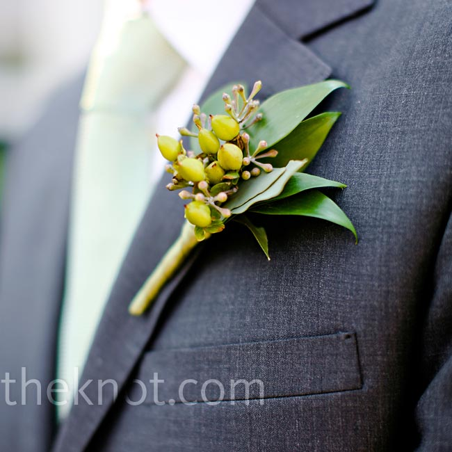 Eoin didn't want his groomsmen to wear flowers on their lapels, so he and Sonya chose simple boutonnieres of only hypericum berries. Though Eoin didn't even want to wear a flower himself, Sonya convinced him to go with a low-key bloom: cream freesia with Italian ruscus to distinguish himself from the other guys.