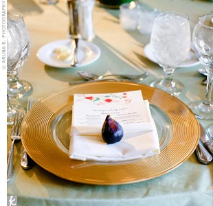 Atop the gold chargers, each place setting had a fig (as a nod to the wedding cake's filling) and a menu card that featured the same design as the invitations.