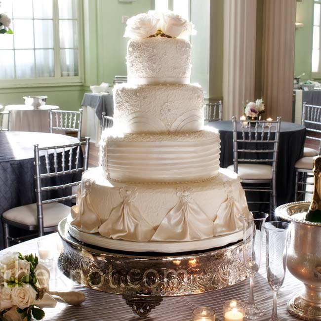 Pearlized fondant draped the couple's stunning all-white cake. A crown of white roses sat atop the four-tiered confection.