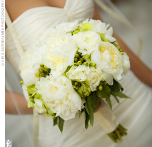Green hypericum berries peaked through the bride's romantic bouquet of white peonies, ranunculus, and green hydrangeas.