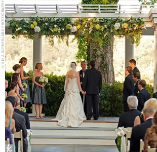 To catch the most romantic outdoor lighting possible, Diana and Eric held their ceremony at 7 pm. They stood on a gray slate floor beneath a large white arbor with the mountains in the distance.