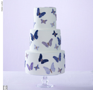 Hand-painted, purple butterflies on a three-tiered fondant wedding cake.
