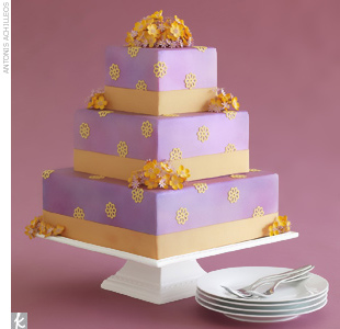 Orange sugard-made flowers scattered along a square, purple fondant wedding cake.