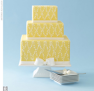 Three-tiered square, yellow fondant wedding cake with an elegant allover frosted pattern and sugar bands and ribbon.
