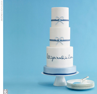 Three-tiered white and blue fondant wedding cake, with laser-printed hand calligraphy and blue bow accents.