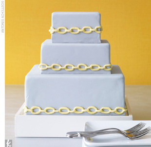Three-tiered square gray fondant cake with yellow chain-link accents.