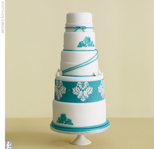 Seven-tiered white fondant wedding cake stacked and accented with aqua bands and a damask applique pattern.