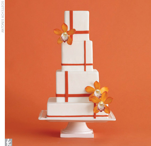 Four-tiered white fondant square wedding cake with orange plaid pattern stripes and bright orange sugar orchid accents.