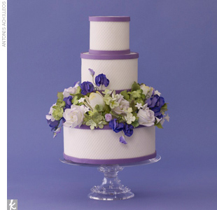 Three-tiered quilted white wedding cake trimmed with purlpe fondant bands and accented with a layer of sugar flowers.