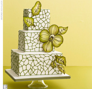 Three-tiered square wedding cake accented with funky green tiling and oversized green flowers.